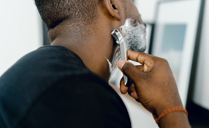 man shaving his face using razor