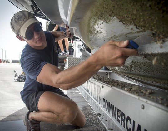 scraping barnacles off bottom of a boat