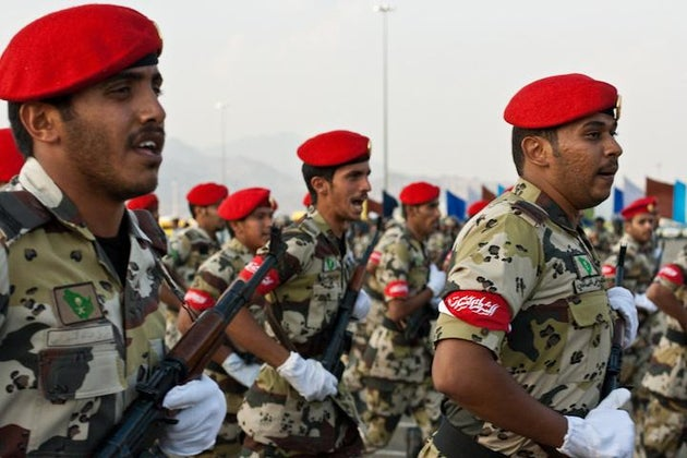 soldiers from saudi arabia wearing white gloves and red hats