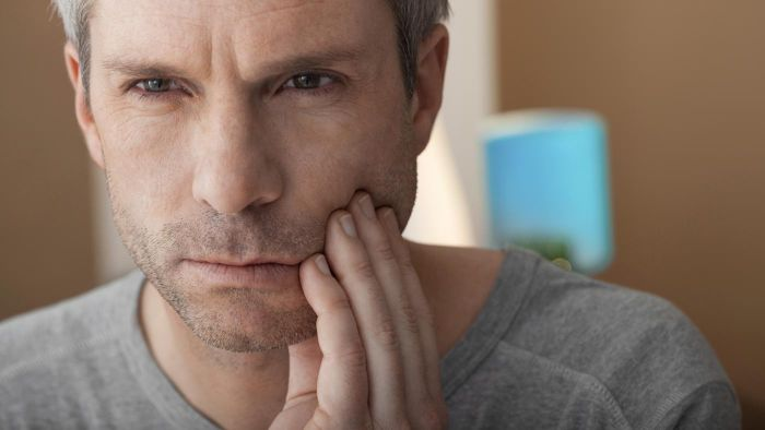 What are some at-home remedies to reduce toothache pain?