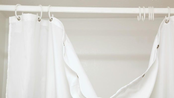 How can mildew be removed from a shower curtain?
