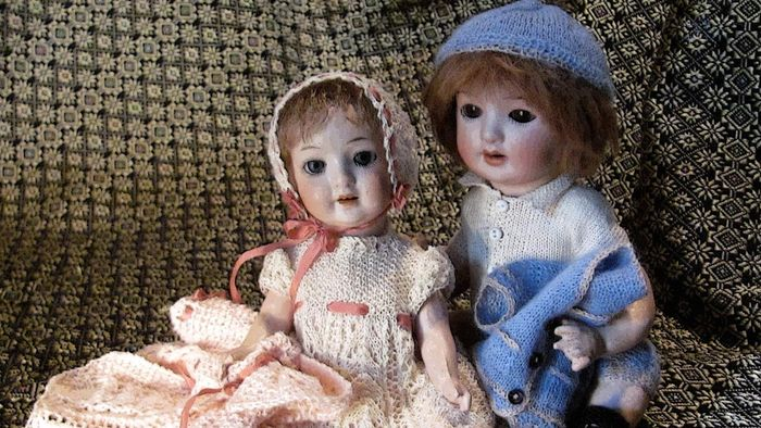 What factors contribute to the value of antique dolls?