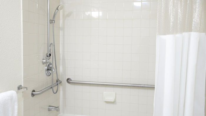 How can a shower grab bar be safely installed?